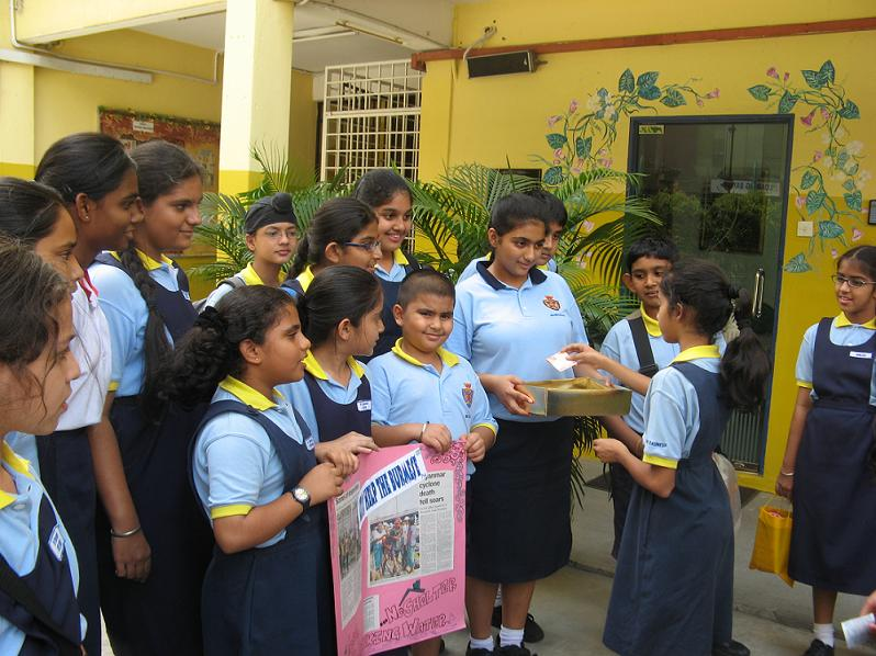 Anmol Shah of Primary 6 giving her generous donation